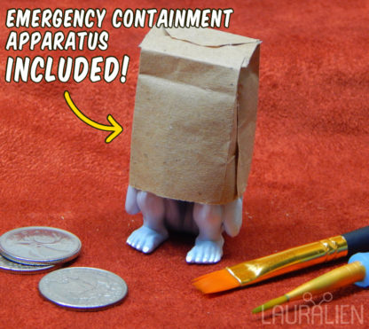 """A small statue of SCP-096. Its upper half is covered by a tiny brown paper bag. Text reads """"Emergency Containment Apparatus Included"""""""