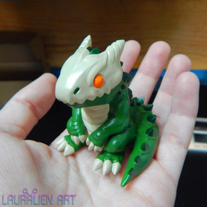 A small, handpainted figurine of SCP-682: a cute lizard monster.