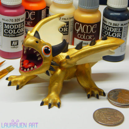 A small statue of a shiny gold dragon. The figurine is roaring, and has large cute eyes.