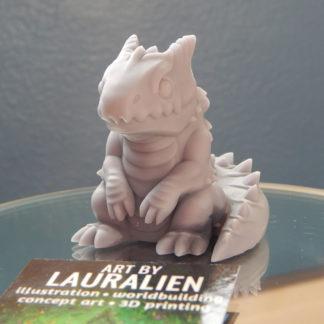 A small, unpainted figurine of a cute lizard monster.