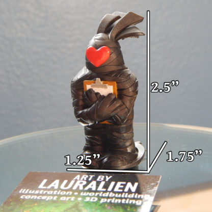 """A small, handpainted figurine of SCP-2521 holding a clipboard with a heart on its face. It measures 2.5"""" tall, 1.25"""" wide, and 1.75"""" deep."""