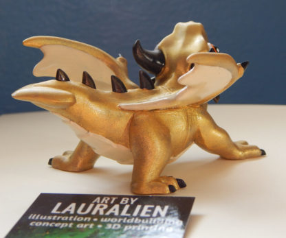A small statue of a shiny gold dragon. The figurine is roaring, and has big cute eyes.