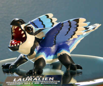 A small statue of a dragon painted to resemble a blue jay. The figurine is roaring, and has big cute eyes.