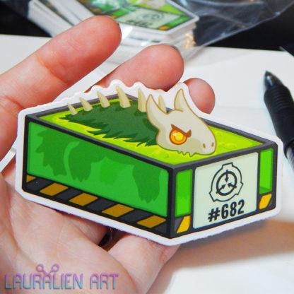 """A 3"""" sticker of a cute cartoon of SCP-682, the lizard monster, in an acid vat"""